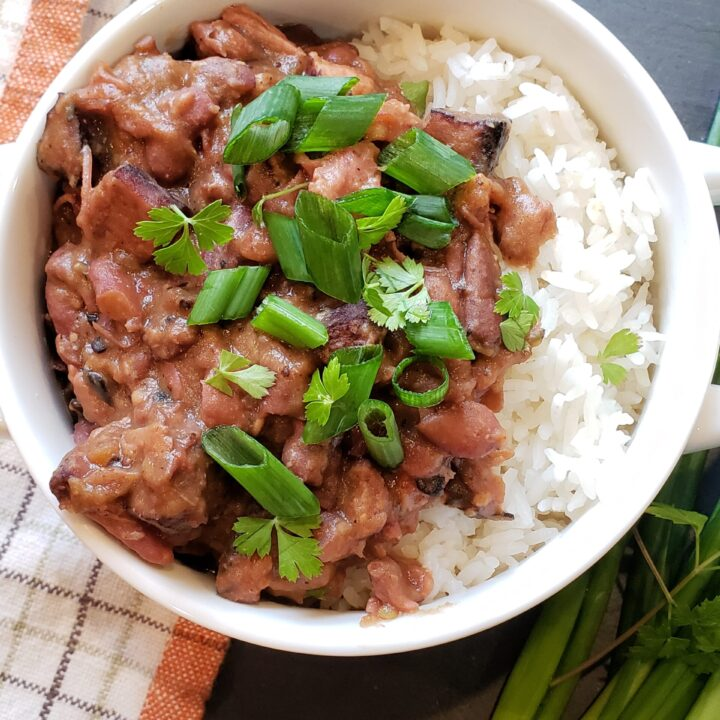 Red Beans and Rice with Diced Green onions on top in a white bowl on a black slate surface with a dish towl and green onions on the surface