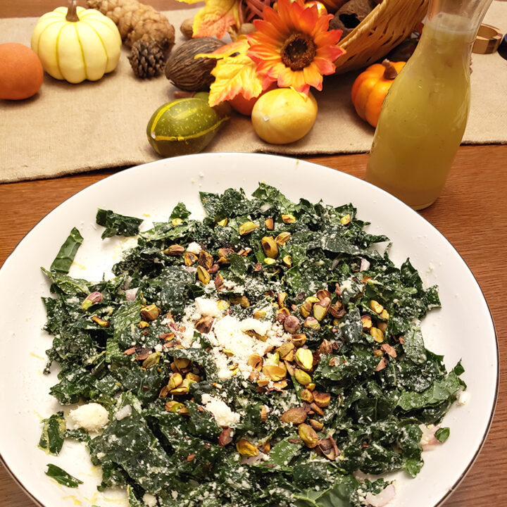 kale salad in a bowl with fall decor in the background