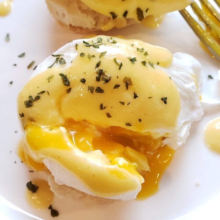 Eggs Benedict on a White Plate with Fork