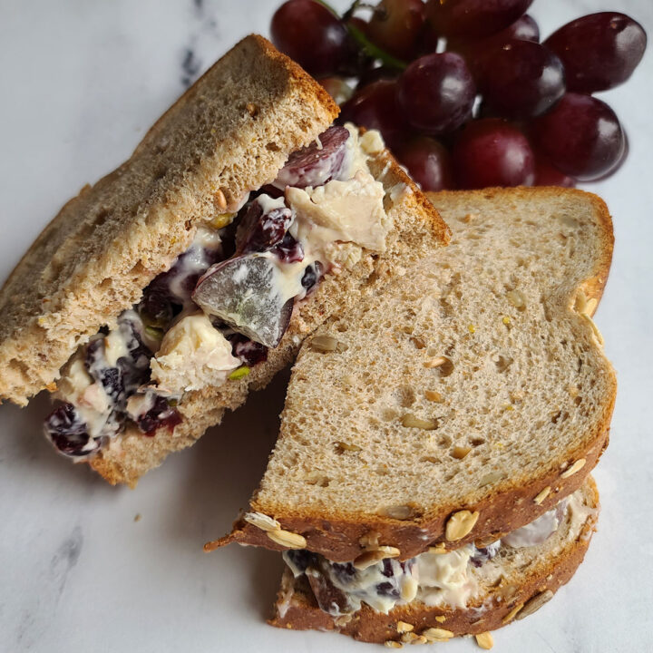 cranberry chicken salad sandwich halves with grapes in background