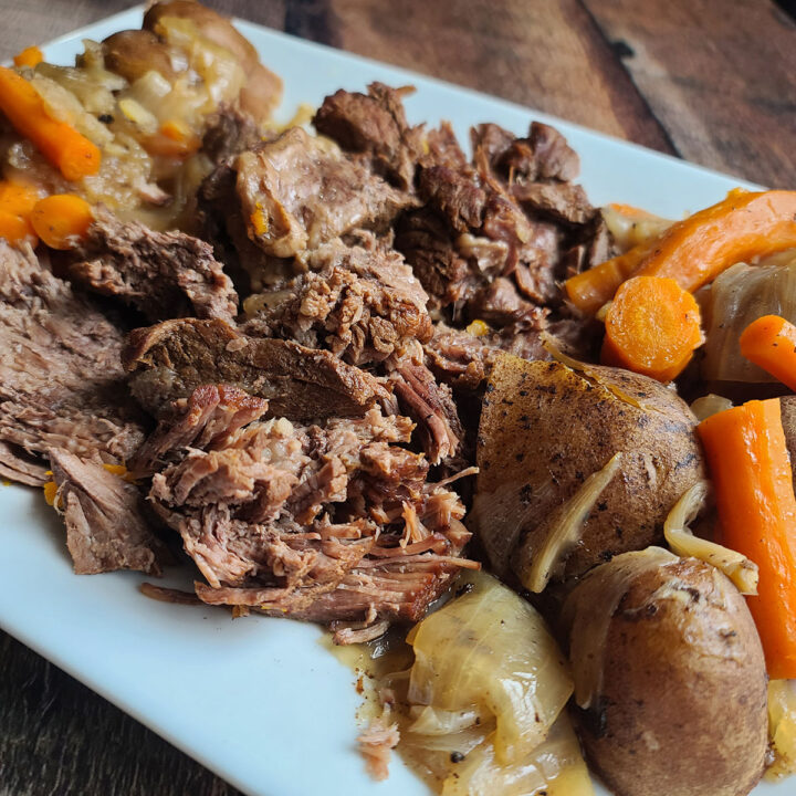 Shredded Instant Pot Pot Roast on a white plate with cooked potatoes, carrots and onions surrounding