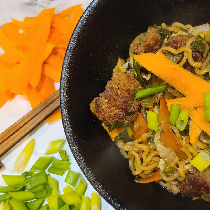 Ginger Meatball Ramen Recipe in a black bowl next to a pile of carrot shavings, pair of chopsticks, and diced green onion tops