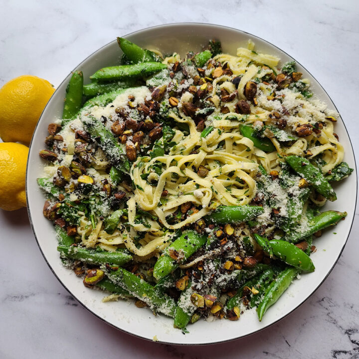 Spinach Pesto and Sugar Snap Pea Linguine topped with pistachios and parmesan cheese in a bowl next to two lemons
